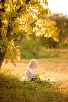 Il bambino gioca nella foresta d'autunno.
