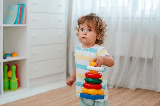 Il bambino gioca sul pavimento della stanza con giocattoli educativi di plastica
