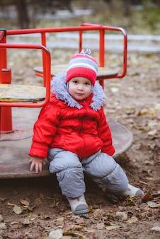 Il bambino gira su un'altalena nel parco giochi nel parco