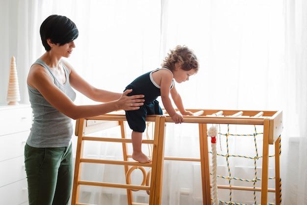 Il bambino in tenera età è impegnato nel complesso sportivo in legno per bambini di casa.