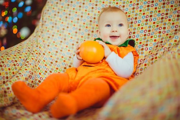 Il bambino in un vestito arancione si trova sulla sedia