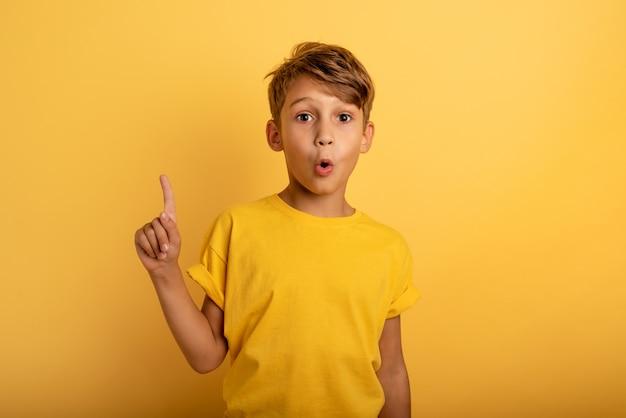 Il bambino indica sopra. espressione stupita e scioccata. sfondo giallo