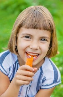 Il bambino mangia il cibo delle carote delle verdure,
