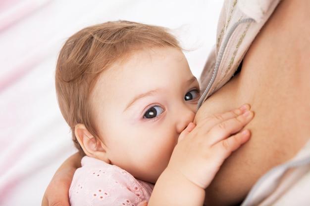 Il bambino mangia il seno della madre.