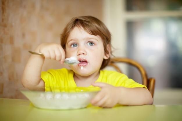 Il bambino mangia latticini con il cucchiaio
