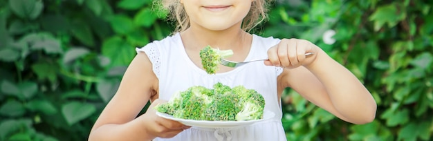 Il bambino mangia le verdure foto d'estate messa a fuoco selettiva