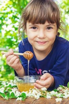 Il bambino mangia miele. messa a fuoco selettiva natura.