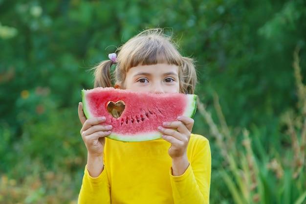 Il bambino mangia un'anguria nel giardino