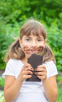 Il bambino mangia una barretta di cioccolato.
