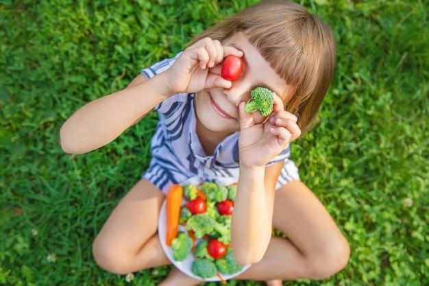 Il bambino mangia verdure broccoli e carote