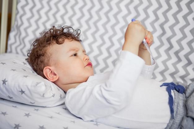 Il bambino misura la temperatura medicina, salute. virus