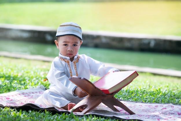 Il bambino musulmano asiatico sta leggendo il corano nel parco, il concetto di islam, vede la macchina fotografica