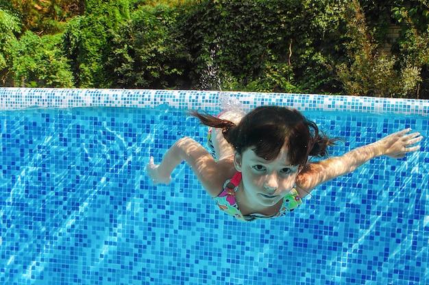 Il bambino nuota in piscina sott'acqua, la ragazza attiva felice si tuffa e si diverte in acqua, fitness per bambini e sport in vacanza in famiglia