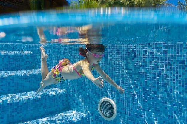 Il bambino nuota in piscina sott'acqua