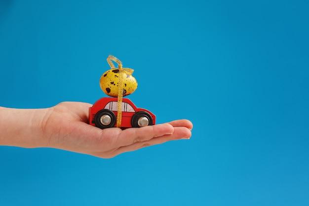 Il bambino passa la tenuta dell'uovo di pasqua sull'automobile.