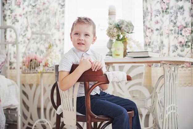 Il bambino piccolo in jeans blu dei pantaloni sta sedendosi sulla sedia di legno nella stanza. fa i compiti. di nuovo a scuola