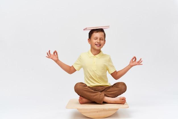 Il bambino piccolo tiene il libro sulla sua testa mentre equilibra sul simulatore speciale