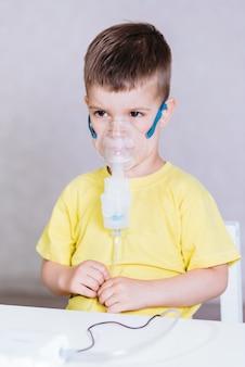 Il bambino piccolo tratta l'inalatore di bronchite a casa