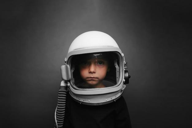 Il bambino piccolo vuole far volare un aeroplano indossando un casco per aeroplano
