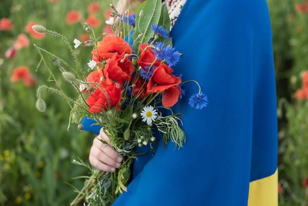 Il bambino porta l'ondeggiamento della bandiera blu e gialla dell'ucraina nel campo del papavero. festa dell'indipendenza dell'ucraina. il giorno della bandiera.