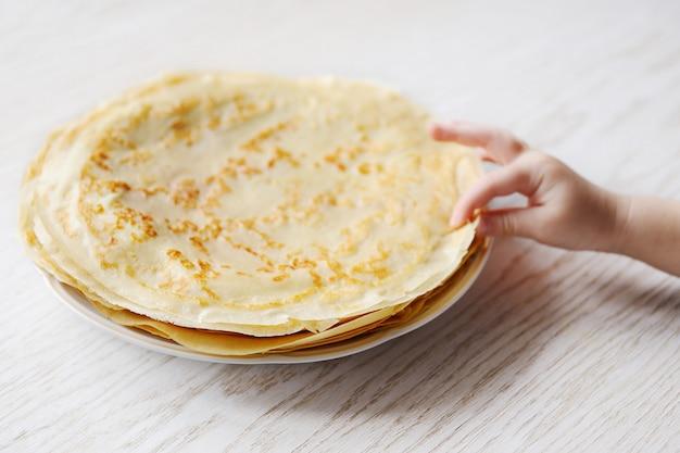 Il bambino prende un pancake da un piatto con i pancake