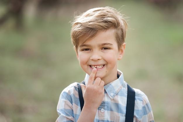 Il bambino punta un dito sul primo dente da latte che è caduto