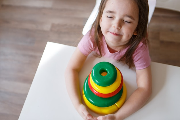 Il bambino raccoglie una piramide. dettagli del giocattolo nelle mani. concetto di sviluppo di abilità motorie, giochi educativi, infanzia, fecondazione in vitro, festa dei bambini, spazio per la copia della scuola materna