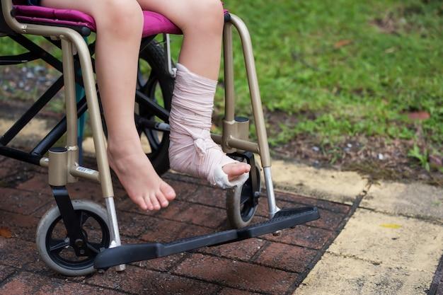 Il bambino rotto la gamba si siede sulla sedia a rotelle