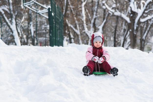 Il bambino scivola giù da una collina su una slitta