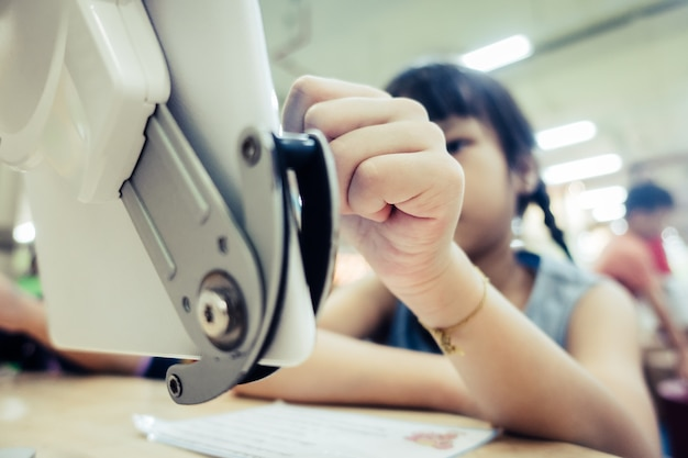 Il bambino serio della ragazza di sguardo sta imparando come usare la compressa digitale