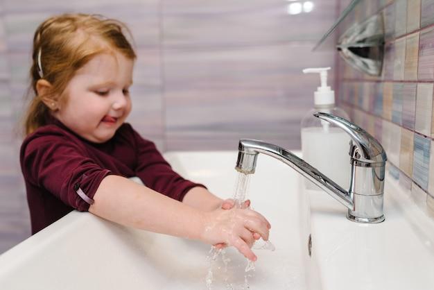 Il bambino si lava le mani con sapone antibatterico