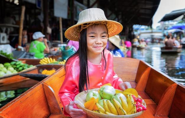 Il bambino si siede sulla barca e tiene il baske di frutta
