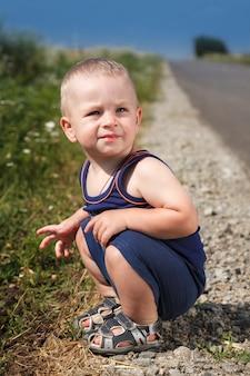 Il bambino si siede sulla strada asfaltata