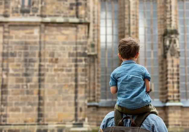 Il bambino si siede sulle spalle del padre mentre cammina per le strade della città vecchia
