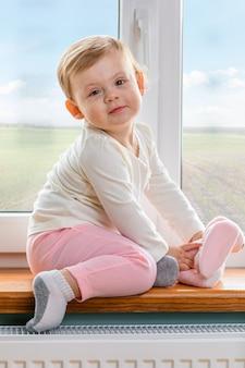 Il bambino si siede vicino a una finestra