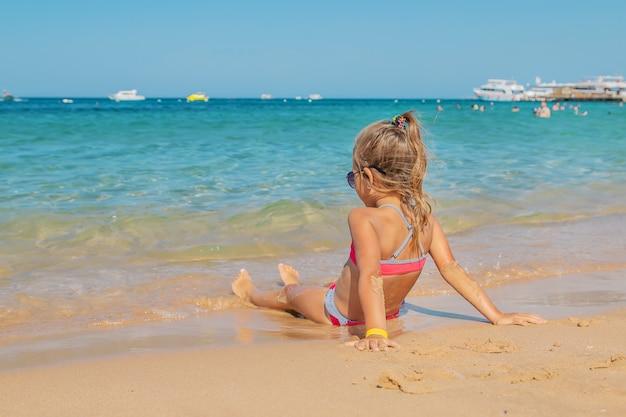 Il bambino si trova nella sabbia sulla spiaggia