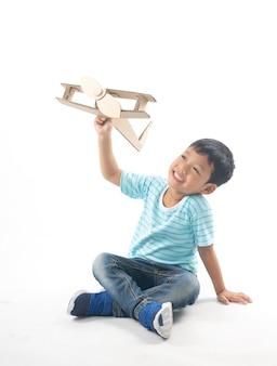 Il bambino sogna come pilota che si siede e che tiene la carta dell'aeroplano isolata su bianco