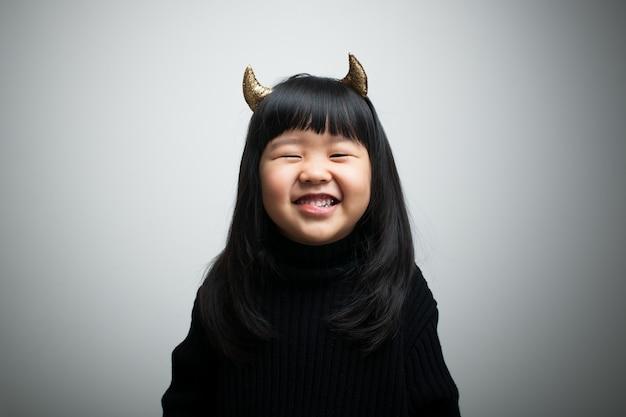 Il bambino sorride brillantemente nel grigio.