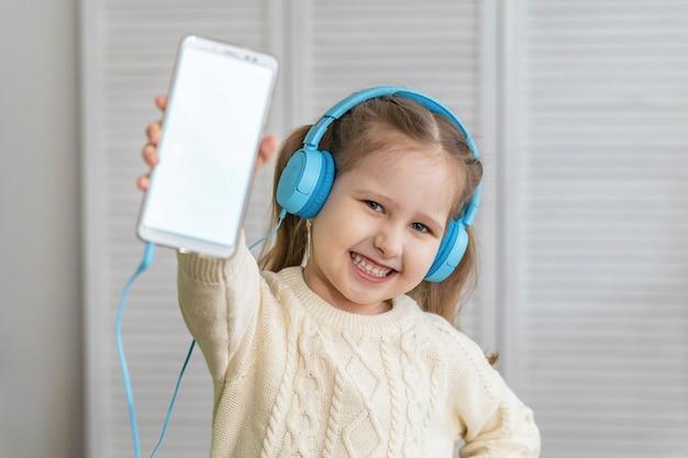 Il bambino sorridente della bambina in cuffie mostra lo schermo in bianco bianco per lo spazio del testo