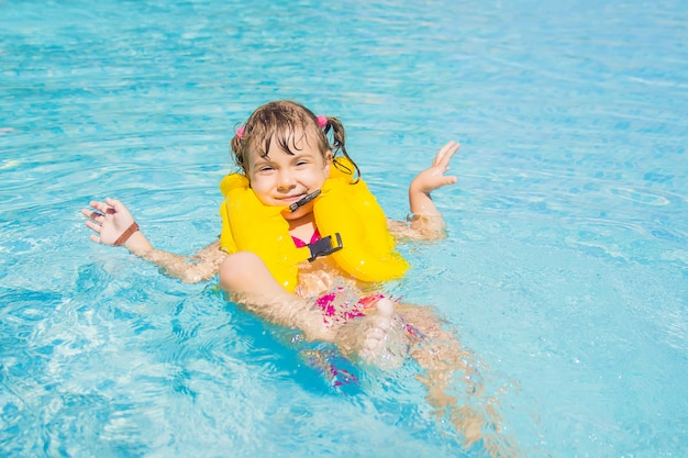 Il bambino sta facendo il bagno nella piscina del resort. messa a fuoco selettiva