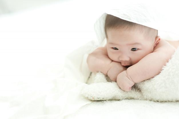 Il bambino sta fissando la parte anteriore su un letto bianco con uno sfondo bianco.
