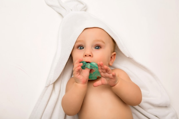 Il bambino sta mentendo con un massaggiagengive in un asciugamano bianco dopo il bagno