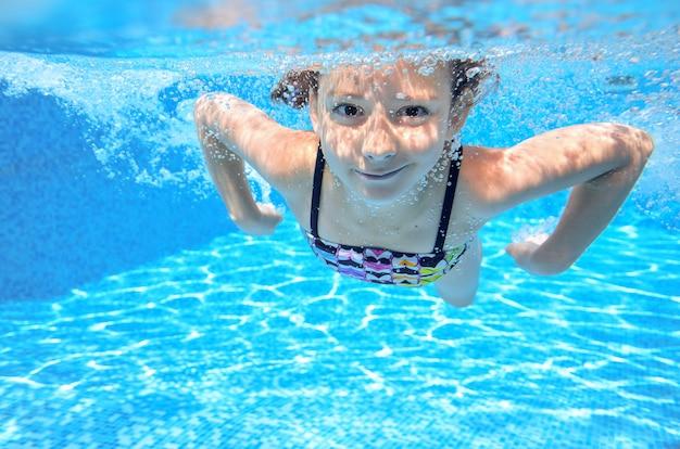 Il bambino subacqueo attivo felice nuota in stagno. bella ragazza sana nuotare e divertirsi in vacanza estiva in famiglia
