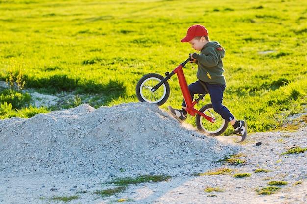 Il bambino sull'equilibrio della bici scala la montagna