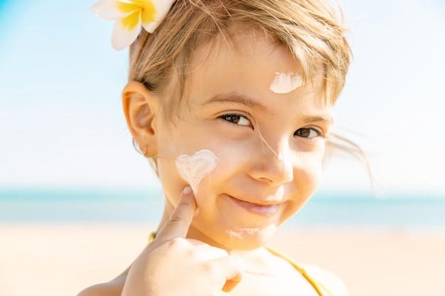 Il bambino sulla spiaggia spalma la crema solare. messa a fuoco selettiva