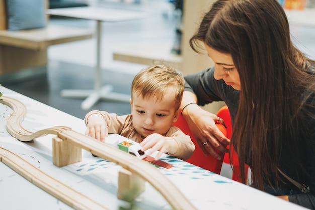 Il bambino sveglio del bambino del neonato con il gioco della madre con l'automobile gioca nella stanza del gioco nel centro commerciale