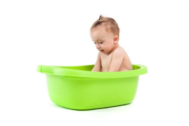 Il bambino sveglio felice prende il bagno in vasca verde