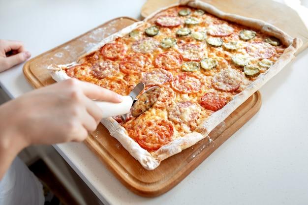 Il bambino taglia la pizza con una fine della taglierina del rullo in su