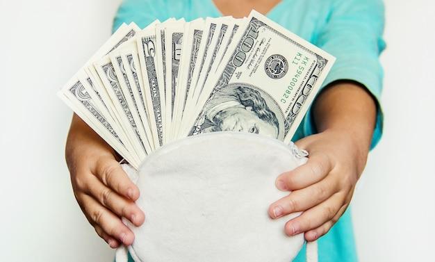 Il bambino tiene i soldi nelle sue mani. messa a fuoco selettiva