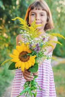 Il bambino tiene in mano un mazzo di fiori di campo